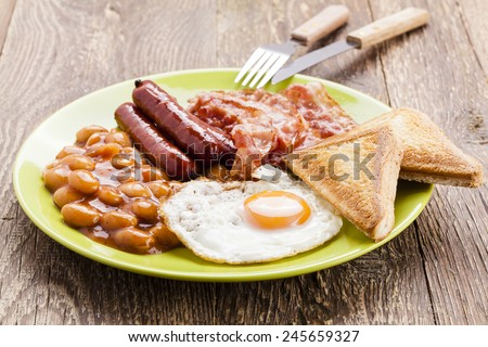 English breakfast with bacon, sausage, fried egg, baked beans and tea or orange juice - stock photo