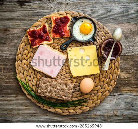 english breakfast with cheese, ham, white and grey bread and jam on wooden background - stock photo