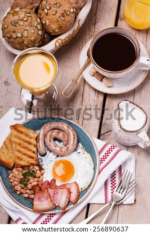 English breakfast with fried eggs, bacon, sausages, beans, toasts and fresh juice.selective focus - stock photo