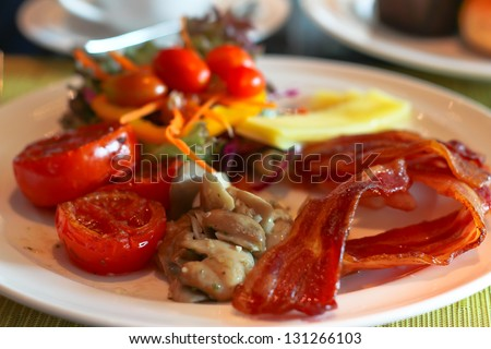 English Breakfast with grilled tomato , bacon ,mushrooms,cheese and salad on Table - stock photo