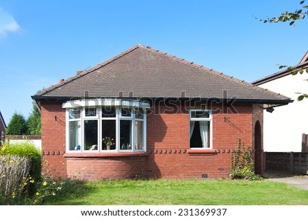 English bungalow house with garden in sunny day - stock photo