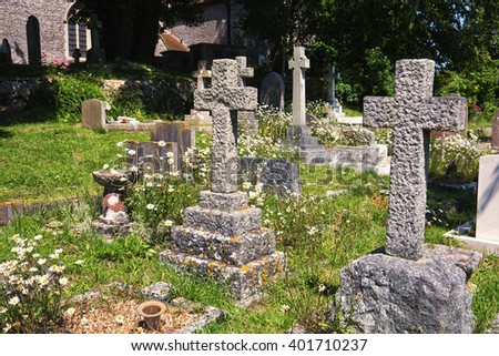 English church graveyard; verdant church yard with church and trees in background  - stock photo