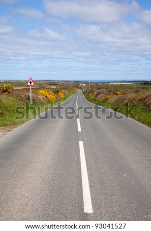 English country road with the sea on the horizon. - stock photo