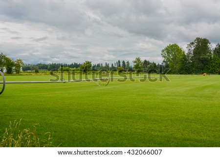 English lawn growing on a farm. Green lawn with irrigation system over the field on cloudy summer day - stock photo
