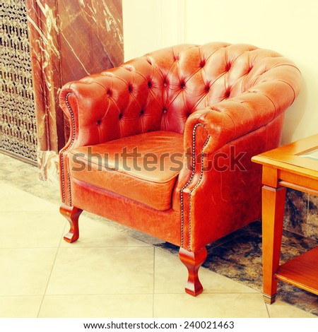 english leather armchair in hotel lobby interior, square toned image, instagram effect - stock photo