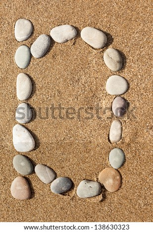 English letters, numbers alphabet stones laid out on the sand - stock photo