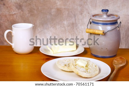 English muffin on vintage wood table with butter and tan background - stock photo
