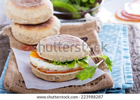 English muffin with egg, cheese and ham for breakfast - stock photo