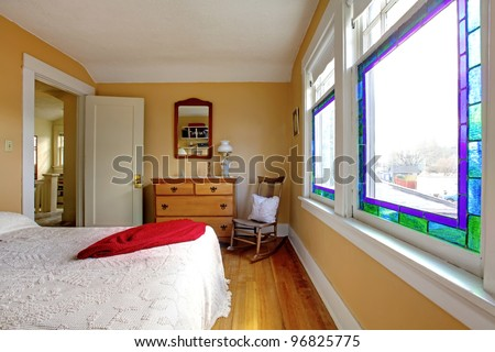 English old bedroom with yellow walls and white bed. - stock photo