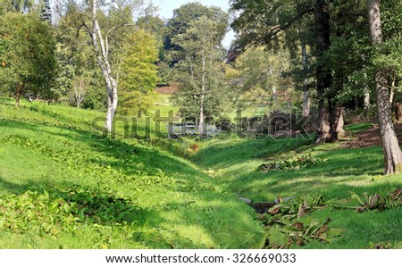 English park with footbridge over a stream   - stock photo