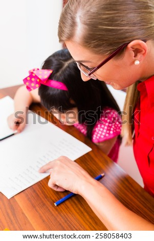 English private teacher helping Asian girl with homework - stock photo