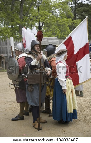 English settler reenactors holding English flag bearing the Cross of St. George as part of the 400th anniversary of the Jamestown Colony, Virginia, at James Fort, Jamestown Settlement, May 4, 2007 - stock photo