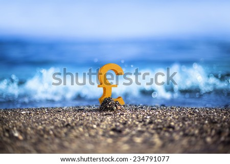 English Sterling currency icon is standing on the wavy sea side - stock photo
