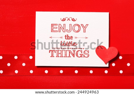 Enjoy the little things text with small red heart - stock photo