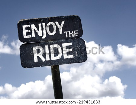 Enjoy The Ride sign with clouds and sky background - stock photo