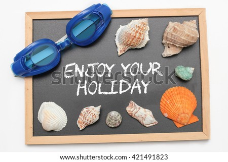 Enjoy Your Holiday text on chalk board with swimming goggle and shell - vacation and business concept - stock photo