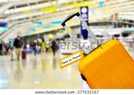 Enjoy Your Week. Orange suitcase with label at airport. - stock photo