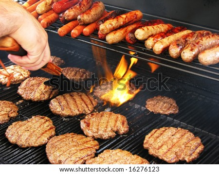 Enjoying a staycation preparing hamburgers and hot dogs. - stock photo