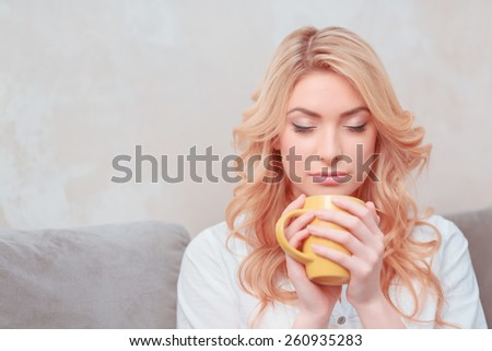 Enjoying aroma. Young smiling woman in casual clothing holding a cup while keeping eyes closed - stock photo