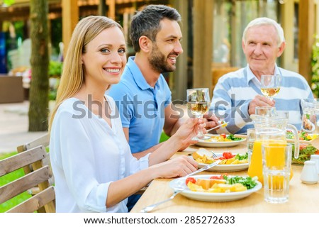 Enjoying dinner with family. Happy family enjoying meal together while woman holding wine glass and smiling  - stock photo