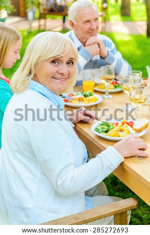 Enjoying dinner with the nearest people. Happy senior woman looking over shoulder and smiling while enjoying dinner outdoors together with her family  - stock photo