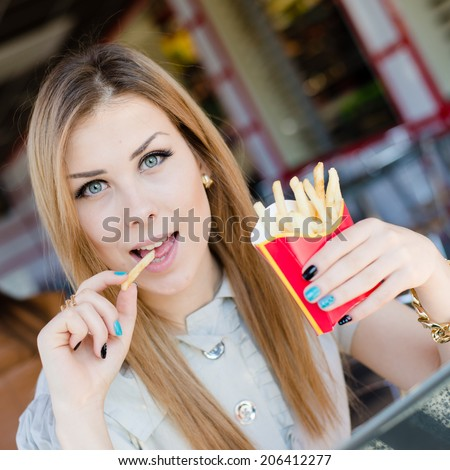 enjoying fast food fries: beautiful young woman cute blond girl having fun eating fried potatoes in restaurant or coffee shop happy smiling & looking at camera close up portrait  - stock photo