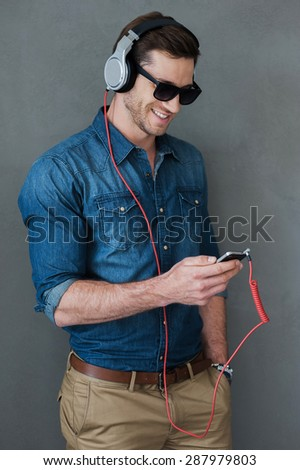 Enjoying favorite music. Cheerful young man in headphones holding MP3 player and looking at it while standing against grey background - stock photo