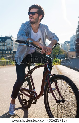 Enjoying freedom. Handsome young man leaning at his bicycle and looking away while standing outdoors  - stock photo