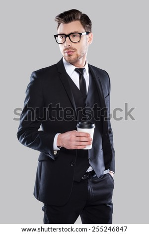 Enjoying fresh coffee. Confident young charming man in formalwear and eyeglasses holding coffee cup and looking away while standing against grey background - stock photo