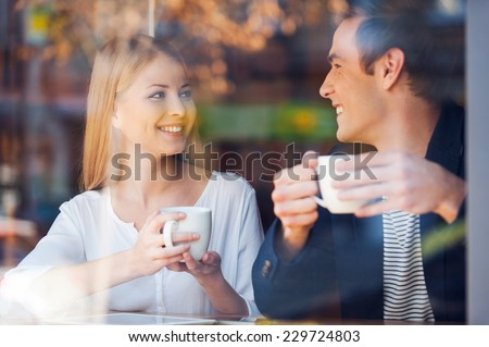 Enjoying fresh coffee together. Through a glass shot of beautiful young couple looking at each other and smiling while enjoying coffee in cafe together  - stock photo