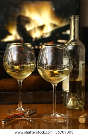 Enjoying glasses of white wine in front of a warm fire - stock photo