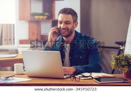 Enjoying good working day. Confident young man working on laptop and talking on the mobile phone while sitting at his working place in office - stock photo