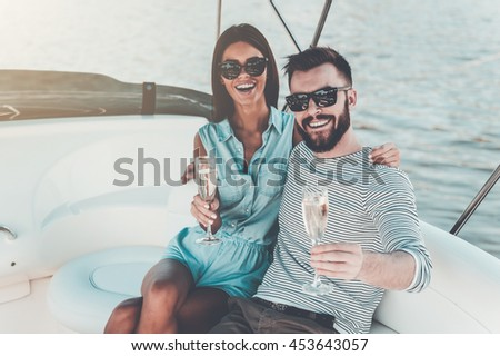 Enjoying great time together. Cheerful young couple holding glasses with champagne and looking at camera while sitting on the board of yacht - stock photo