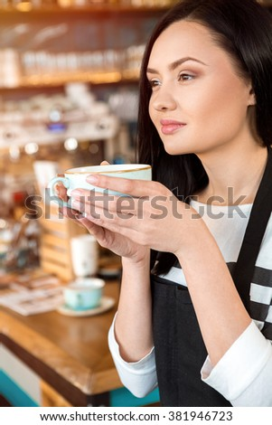 Enjoying her own product. Young female barista smelling coffee aroma holding a cup of beverage posing in a coffee shop - stock photo