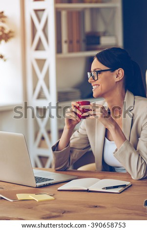 Enjoying her working day. Cheerful young beautiful businesswoman in glasses holding coffee cup and looking away with smile while sitting at her working place - stock photo