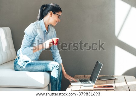 Enjoying her working day. Side view of beautiful cheerful young woman in glasses holding coffee cup and working on laptop with smile while sitting on the couch in office - stock photo