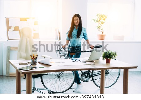 Enjoying her working place. Full length of cheerful young Asian woman leaning to bicycle and looking at camera with smile while standing at her working place - stock photo