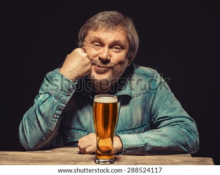 Enjoying his favorite beer.  The front view of handsome satisfied man as fan in denim shirt with glass of beer, sitting at the wooden table. Concept of pleasure and satisfaction - stock photo
