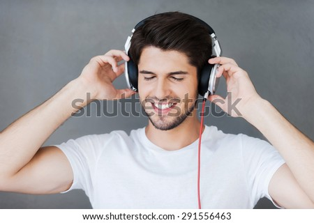 Enjoying his favorite music. Handsome young man keeping eyes closed and adjusting his headphones while standing against grey background - stock photo