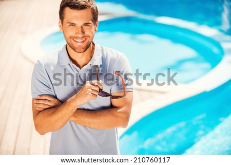 Enjoying his summer vacation. Top view of cheerful young man in polo shirt standing by the pool and smiling to you - stock photo
