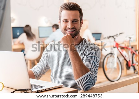 Enjoying his work. Handsome young man looking at camera and smiling while his colleagues working in the background - stock photo