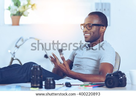 Enjoying his working day. Handsome young African man in casual wear sitting at his working place and working on digital tablet - stock photo