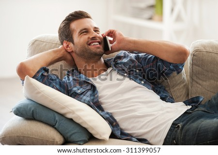 Enjoying leisure day at home. Joyful young man talking on the mobile phone and smiling while lying on sofa - stock photo