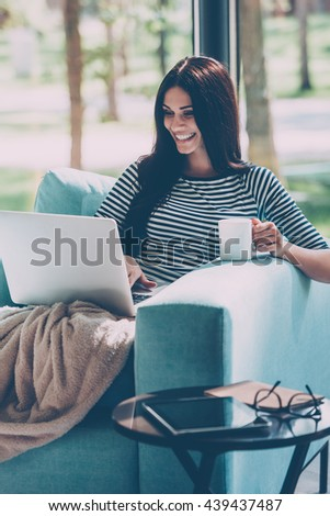 Enjoying leisure time at home. Beautiful young smiling woman working on laptop and drinking coffee while sitting in a big comfortable chair at home  - stock photo