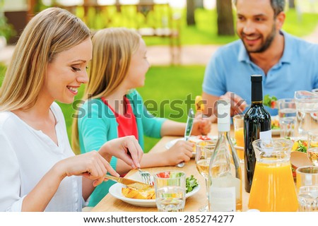 Enjoying meal together. Happy family enjoying meal together while sitting at the dining table outdoors  - stock photo