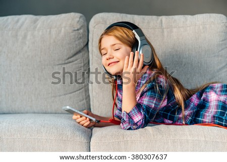 Enjoying music at home. Beautiful little girl adjusting her headphones with smile while lying on front on the couch at home - stock photo