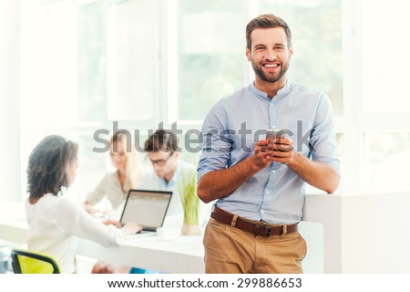 Enjoying office life. Joyful young man holding mobile phone and looking at camera while his colleagues working in the background - stock photo