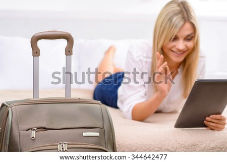 Enjoying oneself. Attractive young woman lying in bed and using her tablet.  - stock photo