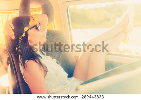 Enjoying perfect day. Beautiful young woman relaxing while sitting on the front seat of her minivan  - stock photo