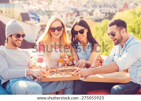 Enjoying pizza with friends. Four young cheerful people eating pizza and drinking beer while sitting at the bean bags on the roof of the building - stock photo